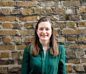Headshot of Kate Mannion, Irish Refugee Council Law Centre Managing Solicitor standing in front of a brick wall