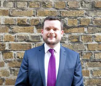 Headshot of Brian Collins, Irish Refugee Council Law Centre Senior Solicitor in front of a brick wall